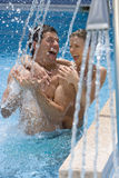 Laughing couple standing under swimming pool shower Royalty Free Stock Photo