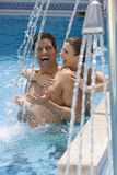 Laughing couple standing under swimming pool shower stock photography