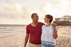 Laughing couple strolling on the beachfront Stock Images