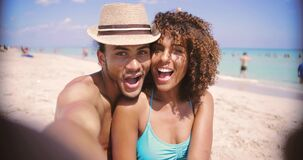 Laughing couple taking selfie. Laughing happy ethnic young man and woman looking at camera and taking selfie on sandy beach at the ocean stock video