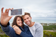 Laughing couple taking a selfie in nature Stock Photo