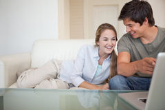Laughing couple using a notebook Stock Images