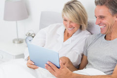 Laughing couple using tablet pc in bed Royalty Free Stock Photo