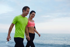 Laughing couple walk along seashore after fitness training. Sport couple walking along the beach resting after workout, sexy fit women and men dressed in Royalty Free Stock Photo
