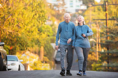 Laughing couple walking along street on hill Royalty Free Stock Photo