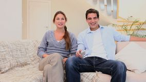 Laughing couple watching television stock video