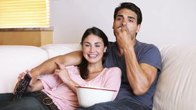 Laughing couple watching the television stock video