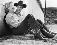 Laughing couple in western attire sitting on the ground Stock Image