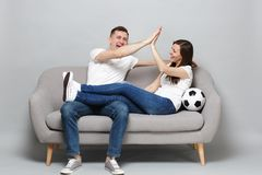 Laughing couple woman man football fans cheer up support favorite team with soccer ball, giving five to each other royalty free stock photos