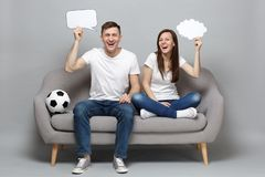 Laughing couple woman man football fans cheer up support favorite team with soccer ball holding empty blank Say cloud. Laughing couple women men football fans stock photos