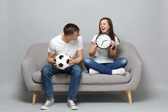Laughing couple woman man football fans in white t-shirt cheer up support favorite team with soccer ball holding round royalty free stock image