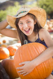 Laughing Cowgirl Holding A Large Pumpkin at the Pumpkin Patch Royalty Free Stock Photos