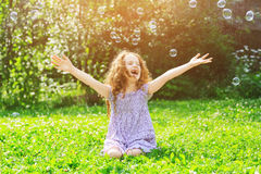 Laughing curly child enjoy soap bubbles. Happy childhood concept. stock photo