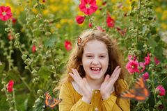 Laughing curly girl with a butterfly on her hair showing white t royalty free stock image
