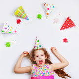Laughing curly girl in carnival party hat, lying on a light back Royalty Free Stock Images