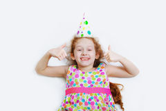 Laughing curly girl in carnival party hat, lying on a light back Stock Photography