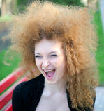 Laughing, curly-haired girl. In the park in spring Royalty Free Stock Image