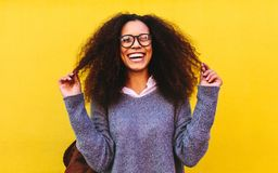 Laughing curly haired woman on yellow background. Portrait of cheerful young african woman with curly hair standing against yellow background. Mixed race female stock images