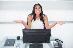 Laughing cute businesswoman sitting behind desk Stock Image