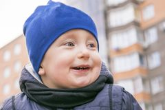Laughing cute child looking away with gladness. Focus on smart nice little boy with amusing smile. Positive kid in stylish blue cap jacket and scarf on walking royalty free stock images