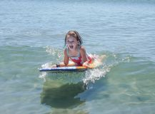 Laughing Cute Little Girl on Boogie Board in Summer. Laughing cute little girl on boogie body board in summer playing in waves Royalty Free Stock Photo