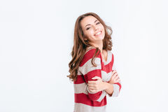Laughing cute woman standing with arms folded. Portrait of a laughing cute woman standing with arms folded isolated on a white background and looking at camera Royalty Free Stock Image