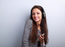Laughing cute young woman in headphones listening the music from Stock Images