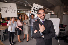 Laughing director showing thumb up, striking employees on backdrop. Stock Images