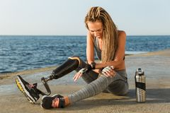 Laughing disabled athlete woman with prosthetic leg. Sitting at the beach with water bottle stock images