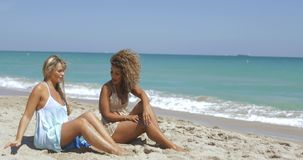 Laughing diverse women chilling on beach. Two multiracial young women in beachwear sitting on sandy shoreline with blue ocean waves and enjoying sunlight stock video footage