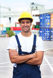 Laughing docker on a seaport. Young docker with crossed arms on a seaport smiling to the camera Royalty Free Stock Images