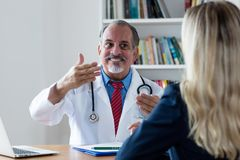 Laughing doctor explaining medical treatment to female patient. At hospital stock photography