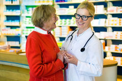 Laughing doctor and happy patient in pharmacy Royalty Free Stock Image