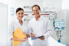 Laughing doctor and nurse posing at hospital room stock images