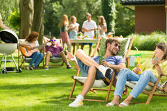Laughing and drinking. Young people laughing and drinking on barbecue royalty free stock image