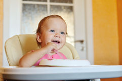 Laughing eating baby. Girl with dirty face Royalty Free Stock Photo