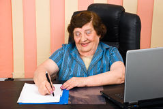 Laughing elder woman write on paper Royalty Free Stock Photo
