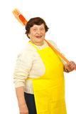 Laughing elderly carrying broom Stock Images
