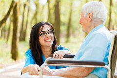 Laughing with Elderly Lady. Kind nurse laughing with elderly patient in wheelchair royalty free stock photos