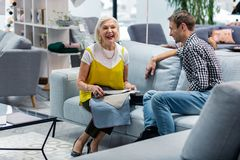 Laughing elderly lady selecting furniture upholstery with smiling handsome son royalty free stock image