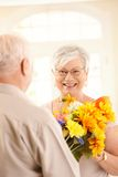 Laughing elderly woman getting bouquet. Laughing elderly women getting flower bouquet, smiling at camera happily Royalty Free Stock Photography