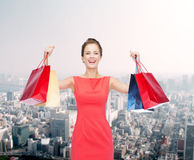 Laughing elegant woman in dress with shopping bags Stock Photography