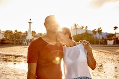 Embracing adult couple sharing a moment. Laughing embracing adult couple on the beach with their arms around each other and hands interlocked, her head on his stock photography