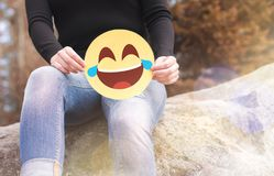 Laughing emoticon with tears of joy. Woman having fun outside and holding a cheerful printed paper smiley face. Happy communication and smiley icon on Royalty Free Stock Images