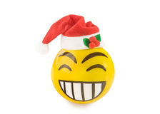 Laughing emoticon toy ball with Santa hat isolated over white. Yellow toy ball in the form of laughing emoticon with Santa hat isolated over white. Christmas Stock Photography