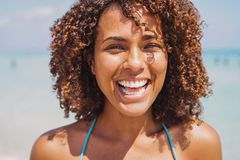 Laughing ethnic woman at the ocean. Laughing young attractive ethnic woman looking at camera on sandy shore at the ocean in sunny day royalty free stock photography