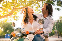 Laughing european couple flirting on scooter Royalty Free Stock Photos