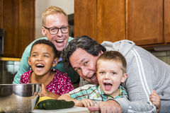 Laughing Family with Gay Dads in Kitchen royalty free stock photo