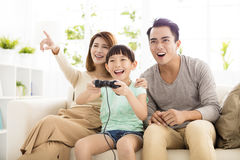 Laughing family playing video games in living room. Laughing asian family playing video games in living room Stock Image