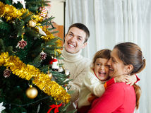Laughing family of three preparing for Christmas Stock Images